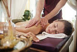 Portrait of beautiful young woman lying on massage table with eyes closed and smiling blissfully enjoying SPA treatment while man massaging her back with lotions and body oils.