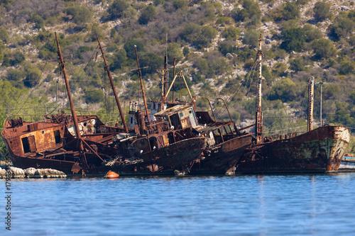 Fotobehang Schip rusty boat wrecks in deep blue water on shore
