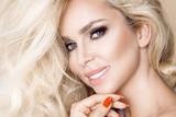 Portret piękna, uśmiechnięta kobieta z długimi blond lokami