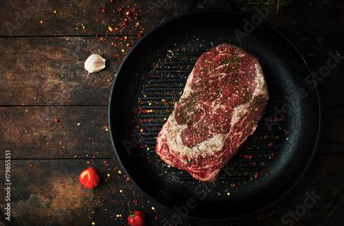Foto op Plexiglas Steakhouse Raw fresh ribeye steak with salt, seasonings, and rosemary in a frying pan