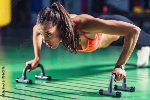 Fototapeta Woman doing push-ups in the gym