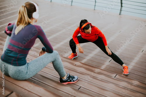 Young woman exercising with a personal trainer outside
