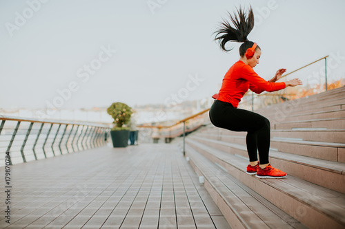 Wall mural Young woman exercising jumping outside