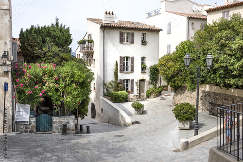 Plagát France, Saint-Tropez, French Riviera, Cote d'Azur: Street scene of quite place in the old town with white house, green trees