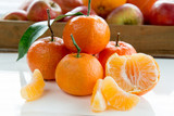 Tangerines and tangerine slices on white table