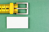 meter belt slimming and blank business card on the green background - 179882978