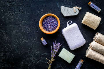 Set for foot spa with lavender. Flowers, spa salt, pumice stone, soap on black background top view copyspace © 9dreamstudio