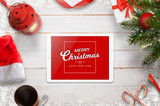Merry Christmas greeting card with tablet, Christmas tree, gifts and decorations. Top view with white wooden desk in background. - 179885748