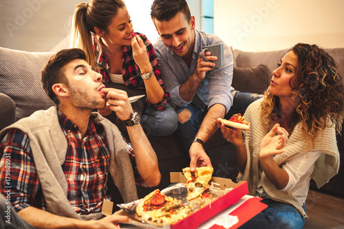 Group of young friends eating pizza.Home party.Fast food concept. Poster