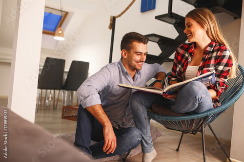 Young couple looking at family photo  album.They sitting in living room and drinks coffee.