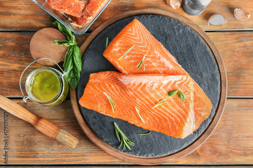 Fresh raw salmon fillet and marinade on wooden table - 179898729