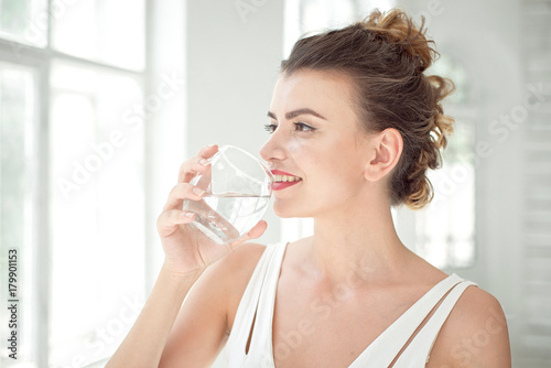 Foto Murales Portrait of a beautiful young woman with a healthy lifestyle smiling while drinking a glass of plain water indoors