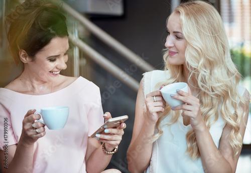 Plexiglas Konrad B. Two cheerful women drinking coffee and looking at the smartphone