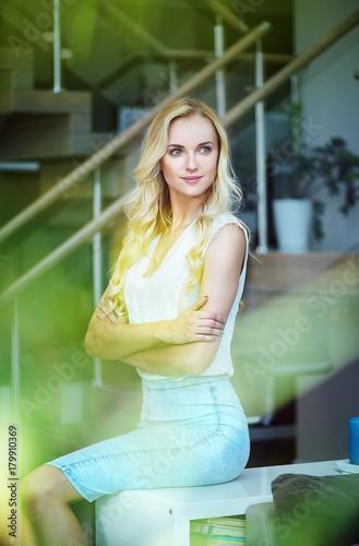 Plexiglas Konrad B. Pretty, alluring woman sitting on the couch