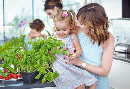 Papiers peints Artiste KB Young moms with their beloved children in the bright, summer kitchen