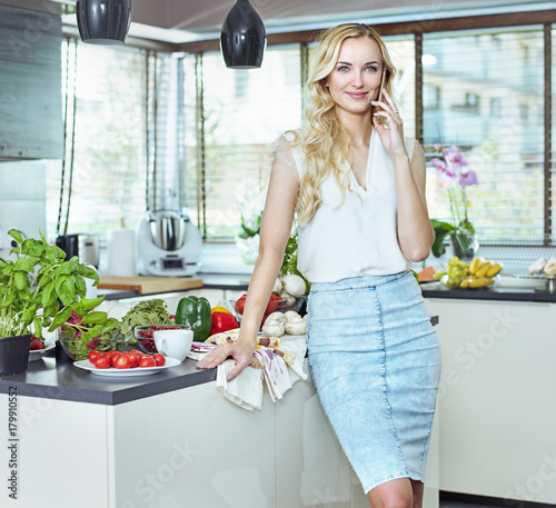 Foto op Canvas Artist KB Pretty, blond lady realxing in the summer kitchen