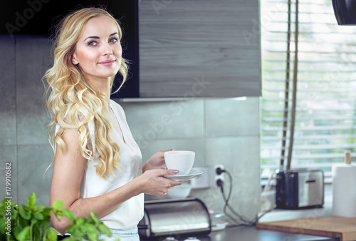 Foto op Canvas Artist KB Portrait of an adorable young woman drinking coffee
