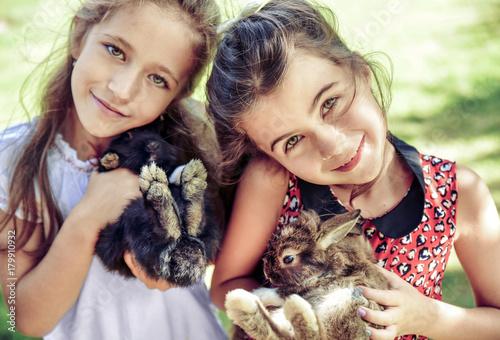 Plexiglas Konrad B. Two cheerful girls hugging fluffy bunnies