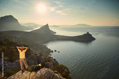Woman hiking mountains and looking at sunset Poster