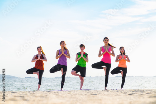Wall mural yoga group of people doing tree pose and namaste with calm relax emotion at beach,Meditation pose,Wellness and Healthy Lifestyle.