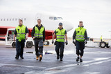 Confident Workers Walking On Runway During Rainy Season - 179944312