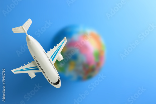 flying around the world / plastic toy plane flying on world globe in blue background