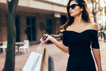 Stylish woman walking on the street with shopping bags