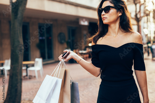 Plakat Stylish woman walking on the street with shopping bags