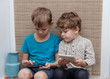 two brothers, ages four and seven play games on smartphone and tablet
