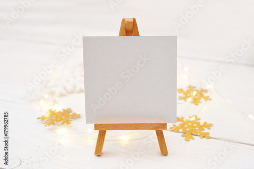 Miniature easel with blank card, pine branches and Christmas decorations. Space for text. top view photo mockup