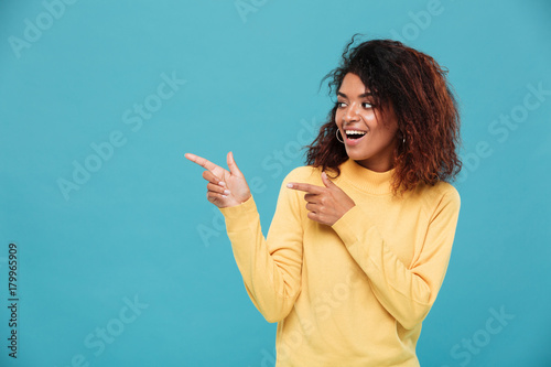 Cheerful young african woman dressed in warm sweater