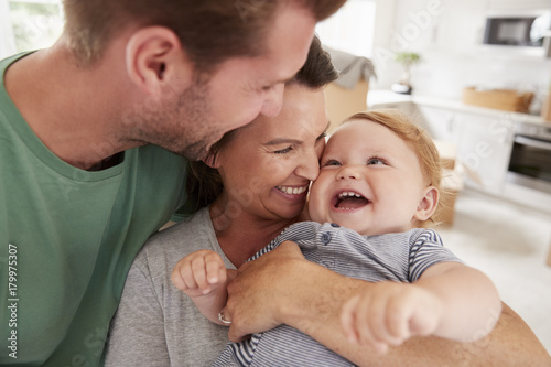 Close Up Of Parents Hugging Happy Baby Son At Home