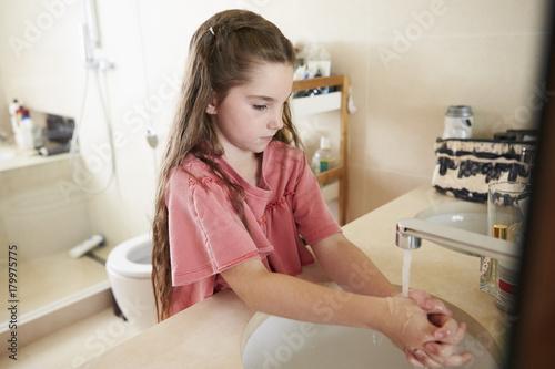 Girl Washing Hands In Bathroom Basin At Home