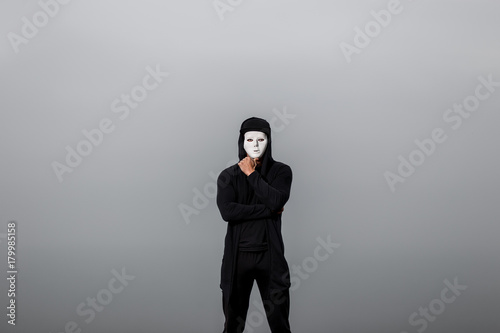 Portrait of man in black hoodie wearing white anonymous mask.