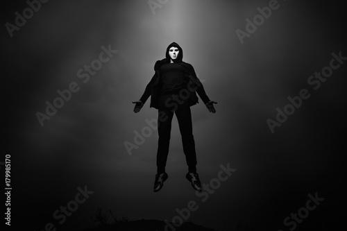 Man in black hoodie wearing white anonymous mask fly up in dark sky.