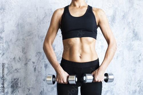 Tuinposter Gymnastiek Muscular woman with barbells on textured wall.