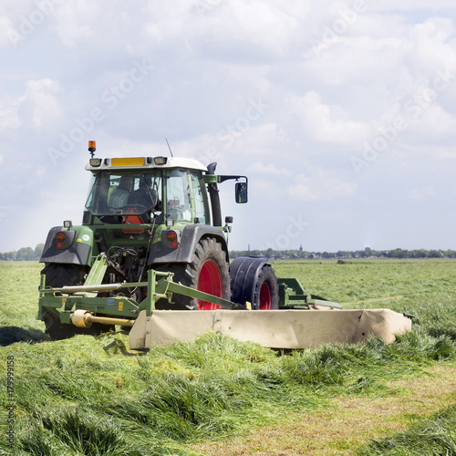 Foto op Plexiglas Gras tractor and mower in green meadow in the netherlands on sunny day