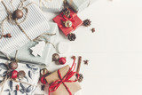 christmas flat lay. wrapped presents with ornaments  and pine cones anise and lights on rustic white wooden background top view, space for text. stylish gifts. seasonal greetings - 180002321