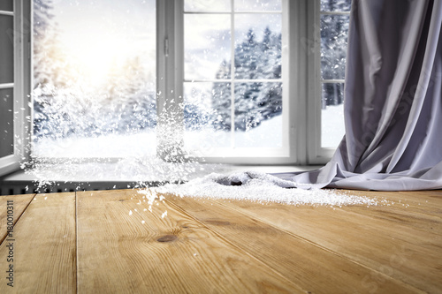Wooden table with space for your product. Curtain in the window. Open window with snowflakes. Landscape of winter forest. Morning sunshine. - 180010311
