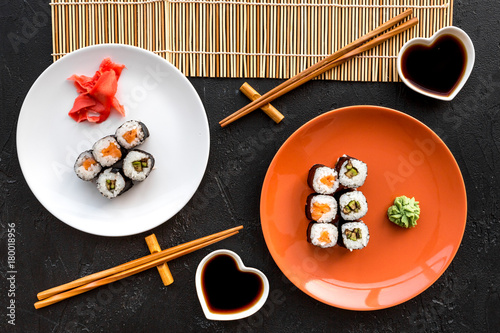 Staande foto Sushi bar Sushi roll with salmon and avocado on plate with soy sauce, chopstick, wasabi on mat on black background top view
