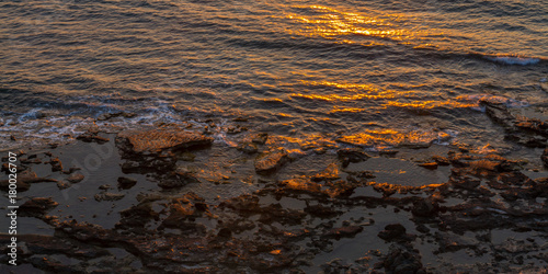 Fotobehang Cyprus Rocky seashore and sun reflections at sunset in Pomos, Cyprus