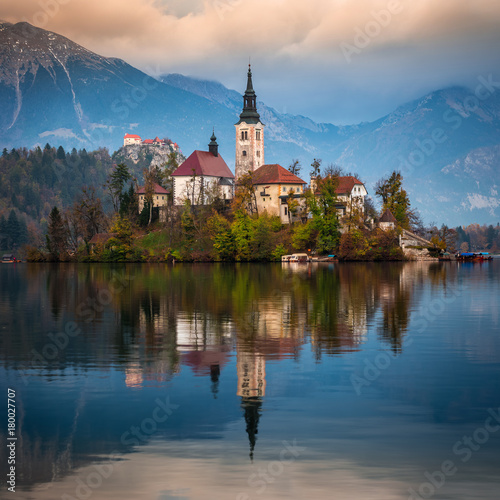 Fotobehang Herfst Bled, Slovenia - Beautiful autumn sunrise at Lake Bled with the famous Pilgrimage Church of the Assumption of Maria with Bled Castle and Julian Alps at background