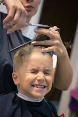 Small kid getting a haircut at hair salon.