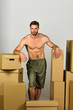 Sexuality and moving in concept: sexy man among boxes.