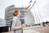 Young woman tourist standing with photo camera in front of the European parliament building in Strasbourg, France - 180045573