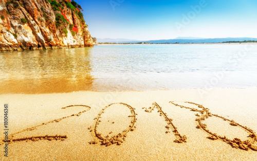 2018 New Year is coming concept. Happy New Year 2018 inscription on the sand of sea beach.