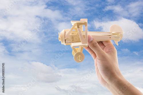 Wood airplane hold hand on sky background