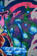 A fragment of detailed graffiti of a drawing made with aerosol paints on a wall of concrete tiles. Background image of street art with fairy blue mushrooms