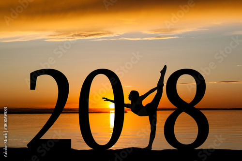 2018 New Year Silhouette of Girl Dancing or Exercising at Golden Sunset or Sunrise