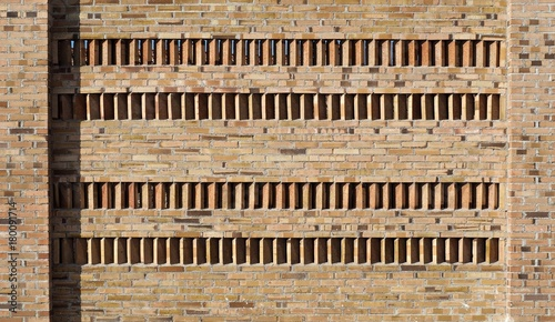 Foto op Canvas Baksteen muur Brick wall with four rows of vertical and angled bricks in the middle